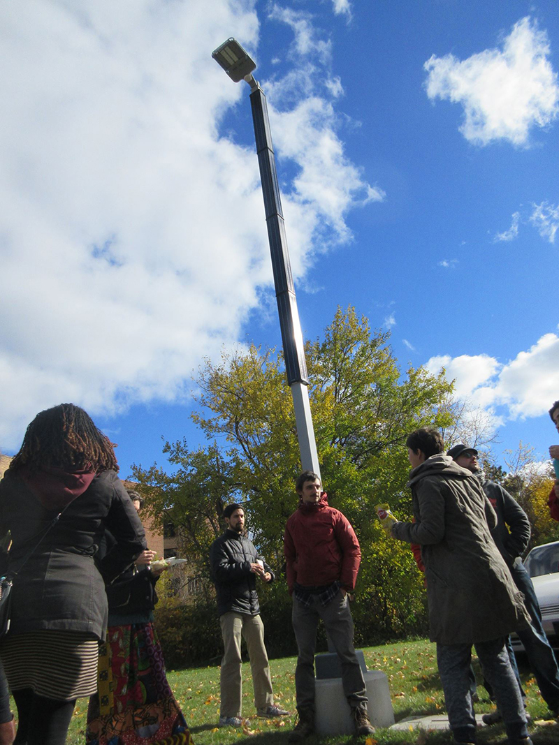 Koeppel speaks to a tour group underneath one of the solar streetlights in Highland Park. Note the panels wrapped around it.