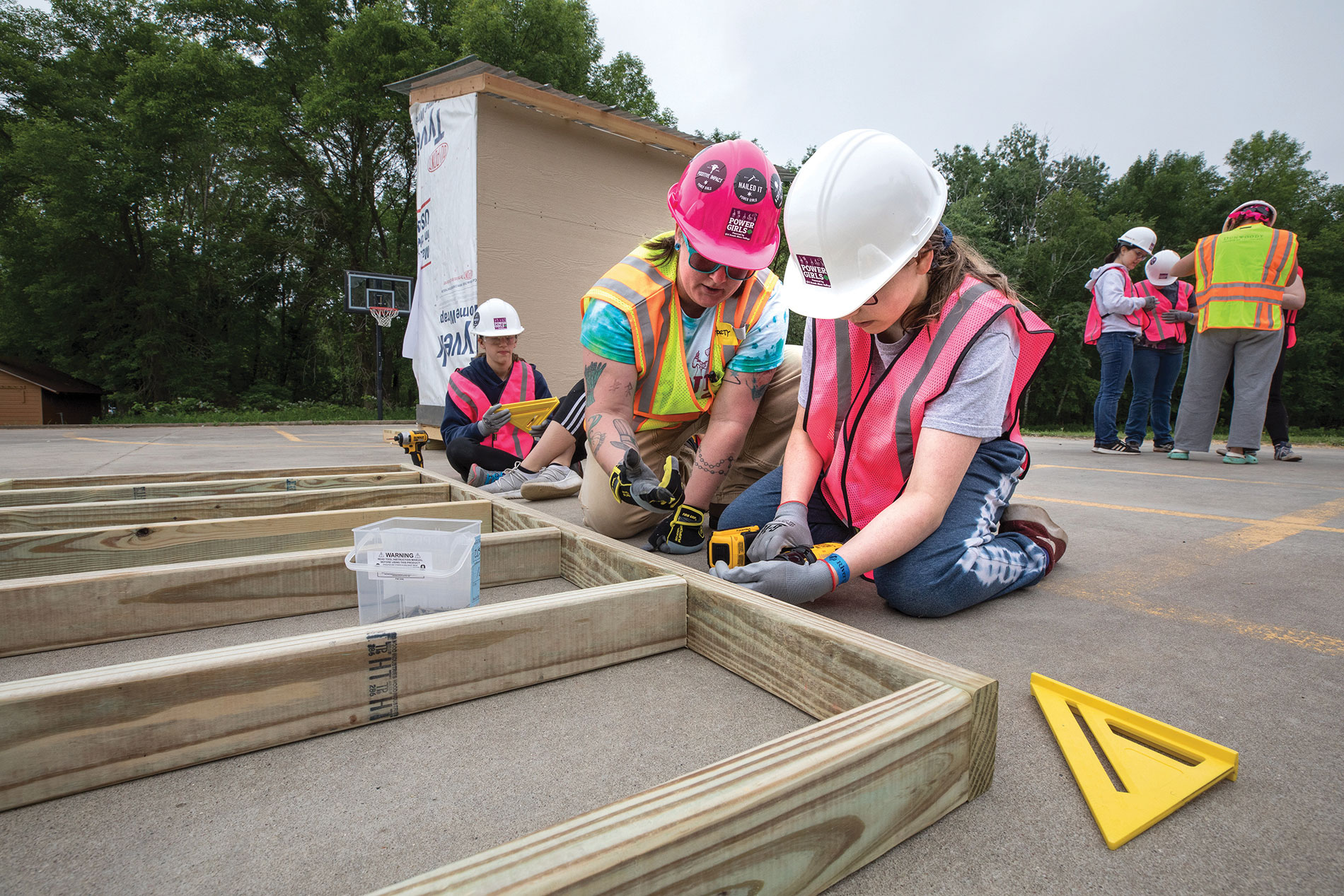 Dunwoody students, graduates and volunteers instruct Girls Scouts on building and finishing tiny houses.