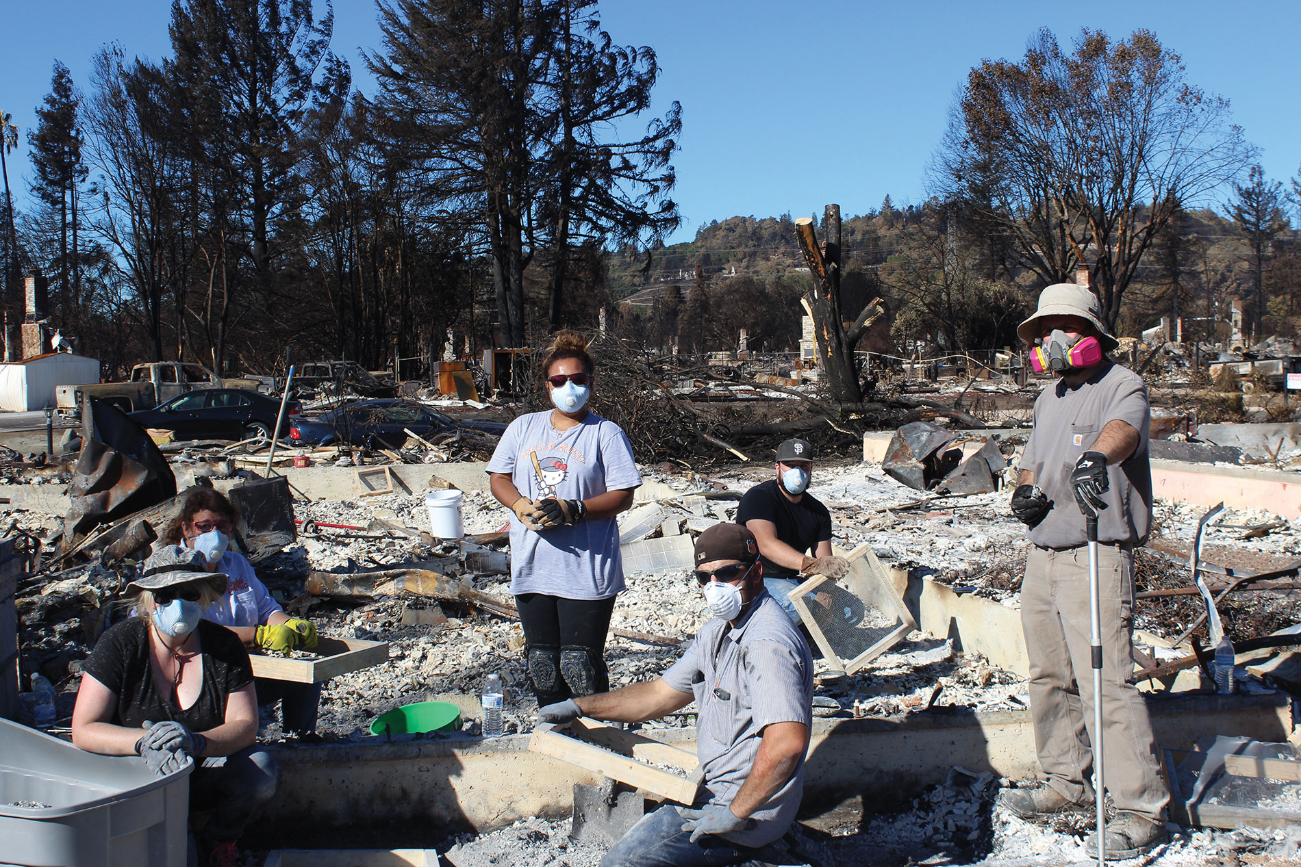 Newlyweds Sean and Megan Corcoran and other members of the Lunardi Electric team clean up what's left of Sean and Megan's home, which burned to the ground after wildfires destroyed their neighborhood last October. Photo courtesy of Joe Lunardi Electric Co.