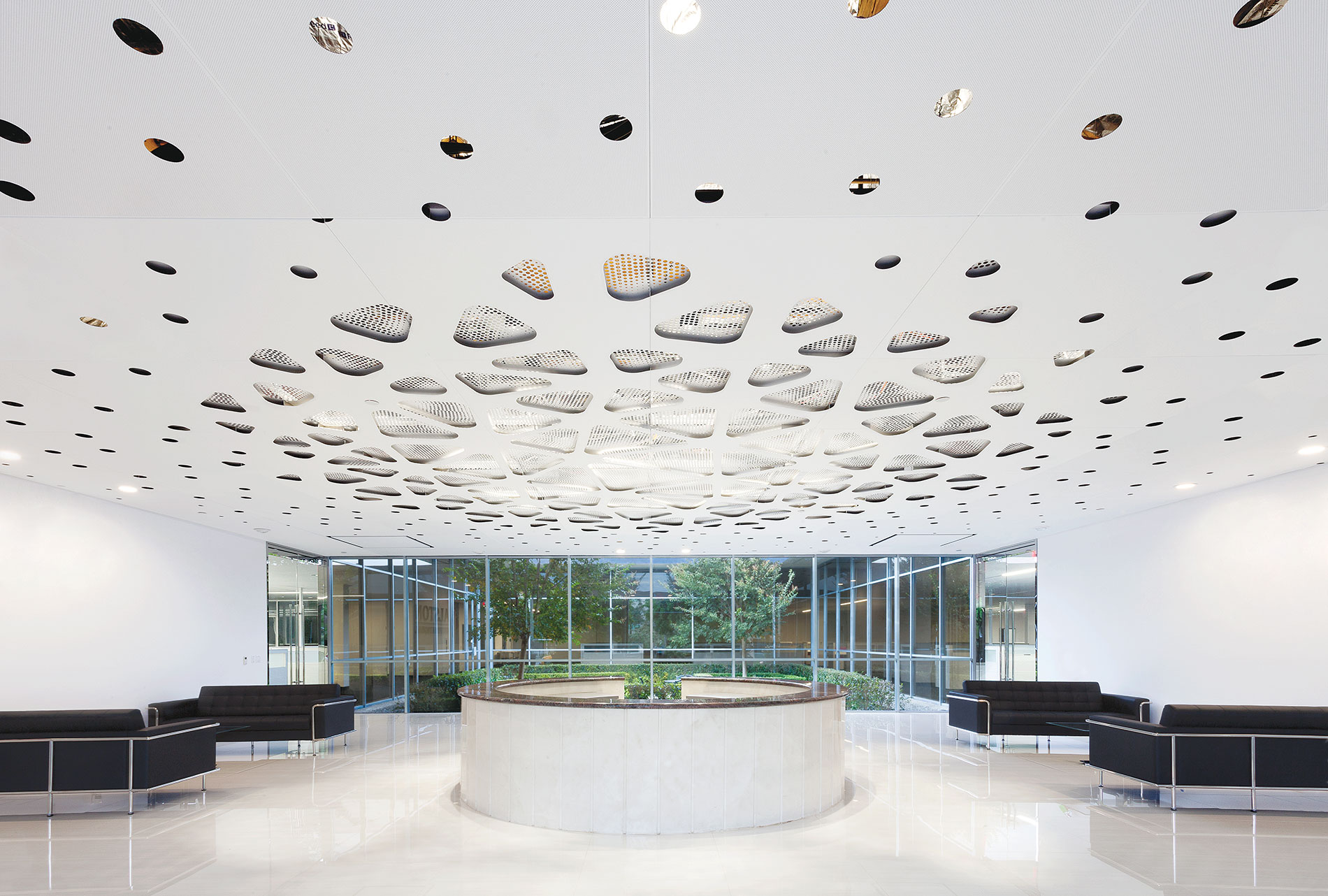 USG's Parti dual-layer acoustic ceiling has integrated lighting and a custom perforated design. Image Courtesy of USG Ceiling Plus