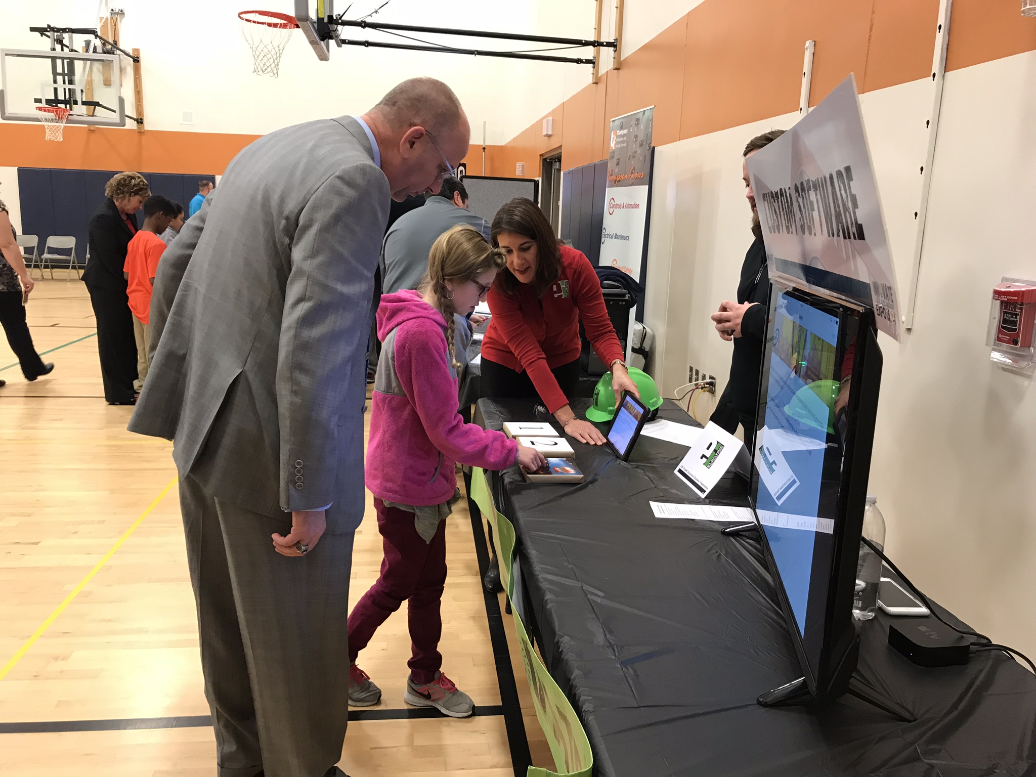 Tasha Barker, General Manager of Electric Innovations, sister company of Thompson Electric, explains a new application they designed, to a student and Dr. Paul Gausmann, Superintendent of Sioux City Schools.