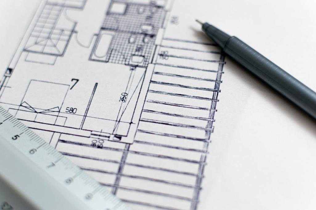 A black & white construction blueprint with a pen and rule laying on top of the paper