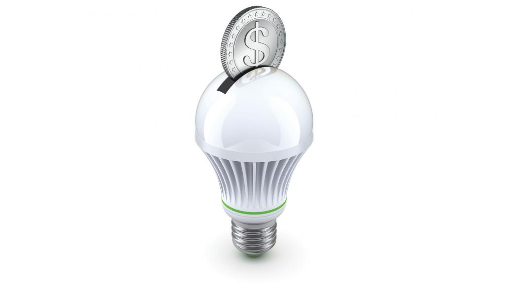 Lightbulb with a slot in it like a piggybank with a coin resting in the slot.