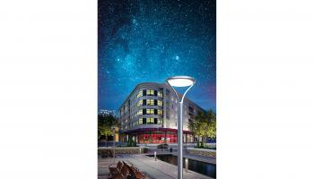 Image of a building, sidewalks, landscaping and outdoor lighting against a night sky full of stars | Lithonia Lighting