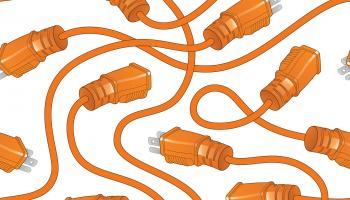 Orange electrical cords with plugs overlaying each other | iStock / Filo