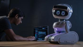 A small, cute robot sits on a table while a man hunches over a computer in the background | Misty Robotics