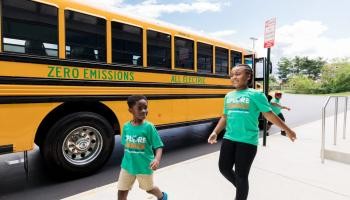 Two children walk past a school bus which reads Zero Emissions all electric along the side.