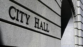 "Close up of a building entrance with ""City Hall"" printed on it"