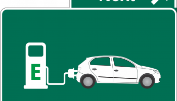 "An illustration of an electric car plugged in to a charging station, on a green highway sign that says ""Next"""