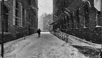A person walks down an empty snow-covered street during a snow storm