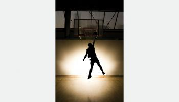 A backlit basketball player does a slam dunk | Shutterstock / S Pytel