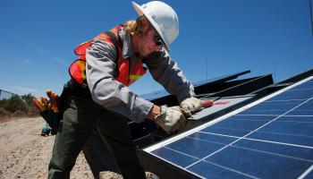 A male worker installing solar panels