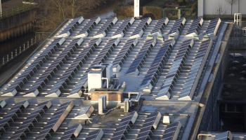 Solar panels laid out on a flat roof of a commercial building