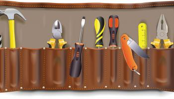 Tool pouch filled with various tools like a hammer, screwdrivers and wire strippers