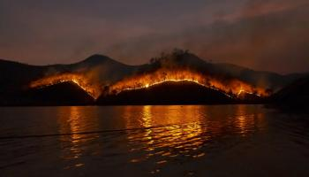 A wildfire burns through hills at night