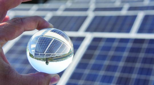 A transparent circular ball reflecting solar panels.