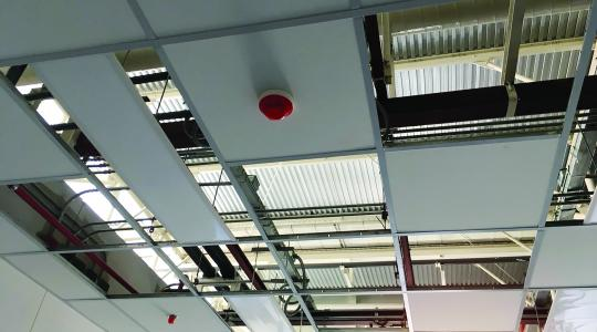 A ceiling fire alarm in commercial space.
