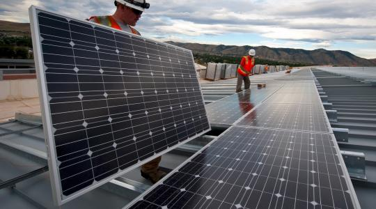 Two contractors installing solar panels on a roof