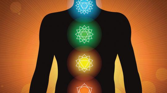 A silhouette of a human body overlaid with symbols for the 7 chakras | Getty Images / Shoo_Arts