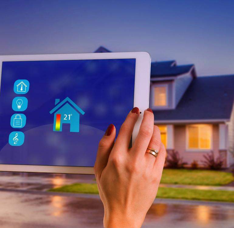 A person's hands holding a tablet showing a smart home heating system, with the home in the background